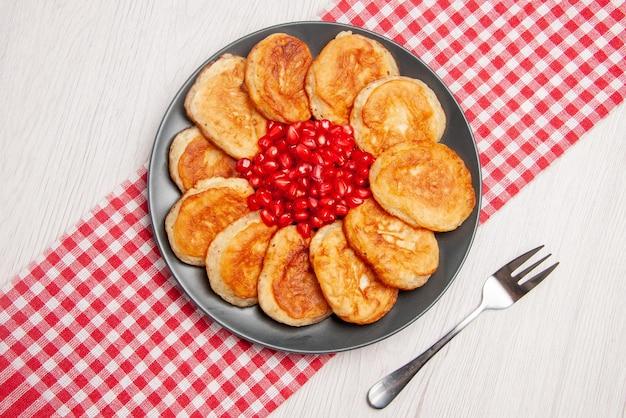 Bovenaanzicht granaatappelpannenkoekjes en zaden van granaatappel op het geruite tafelkleed en een vork op tafel