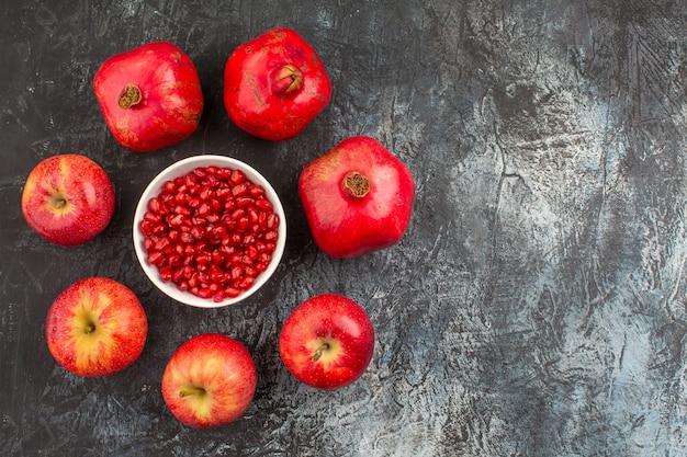 Bovenaanzicht granaatappels appels granaatappels rond een kom met zaden van granaatappel