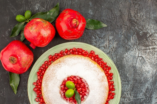 Bovenaanzicht granaatappels een cake met zaden van granaatappel en drie granaatappels met bladeren