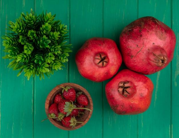 Bovenaanzicht granaatappels met aardbeien op groene muur