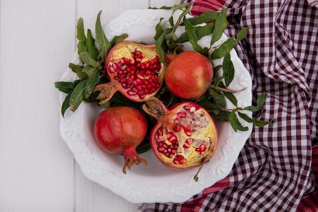 Bovenaanzicht granaatappels met bladeren in een witte plaat en een geruite handdoek op een witte achtergrond