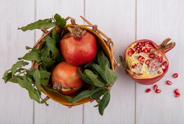 Bovenaanzicht granaatappels met takken van bladeren in een mand op een witte achtergrond