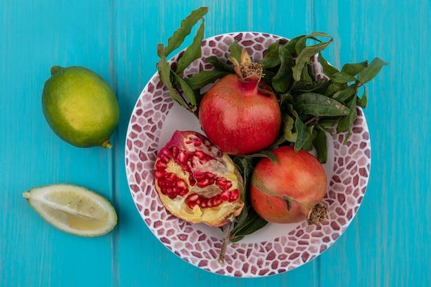 Bovenaanzicht granaatappels op een bord met limoen op een turkooizen achtergrond