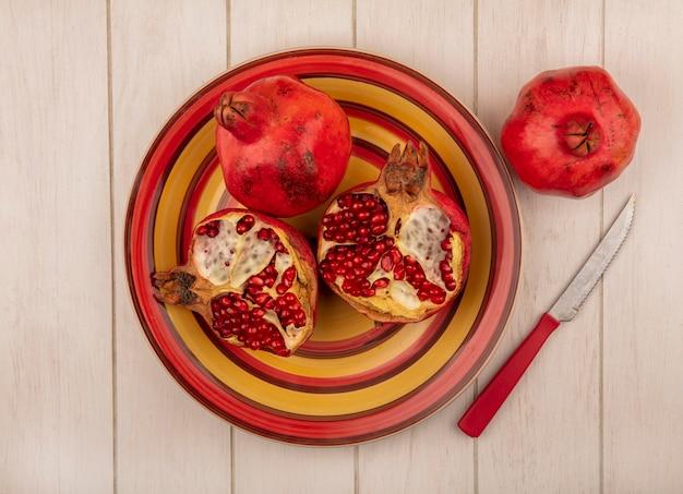 Bovenaanzicht granaatappels op een rode en gele plaat met een mes