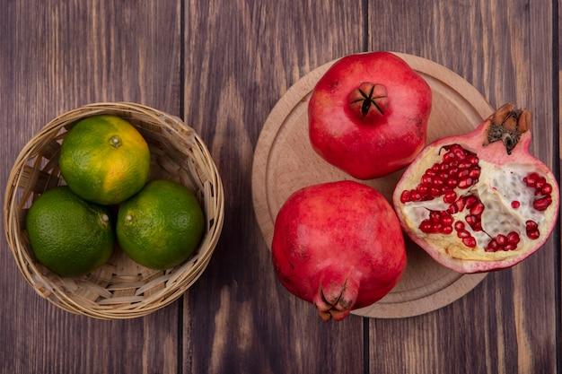 Bovenaanzicht granaatappels op een stand met mandarijnen in een mand op een houten tafel