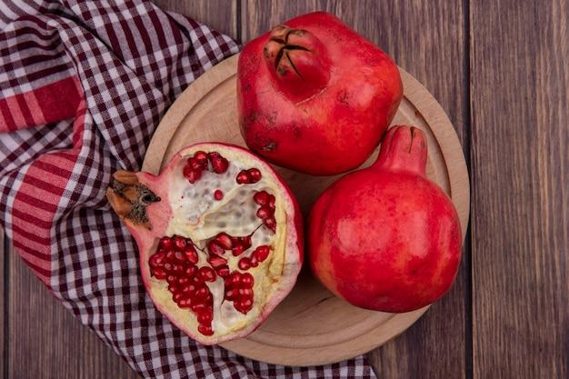 Bovenaanzicht granaatappels op een standaard op een rode geruite handdoek op een houten tafel