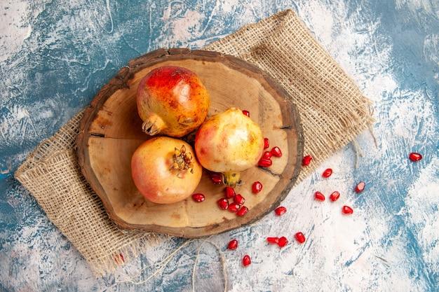 Bovenaanzicht granaatappels op ronde snijplank verspreid granaatappelpitjes op blauw-wit oppervlak