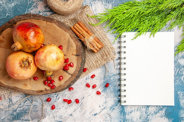 Bovenaanzicht granaatappels op ronde snijplank verspreide granaatappelzaden een notitieboekje kaneel op blauw-witte achtergrond