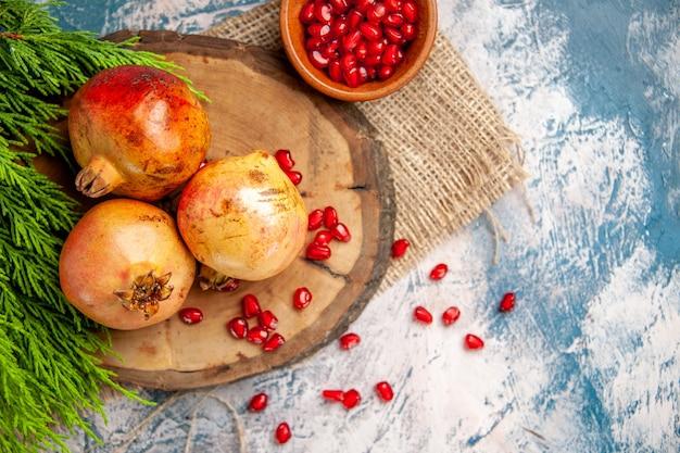 Bovenaanzicht granaatappels op ronde snijplank verspreide granaatappelzaden in kom op blauw-witte achtergrond