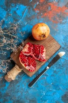 Bovenaanzicht granaatappels op snijplank dinermes op blauwe ondergrond