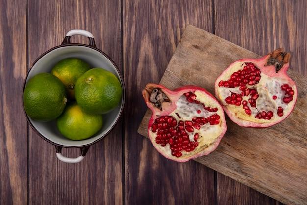 Bovenaanzicht granaatappels op snijplank met mandarijnen in een pan op houten tafel