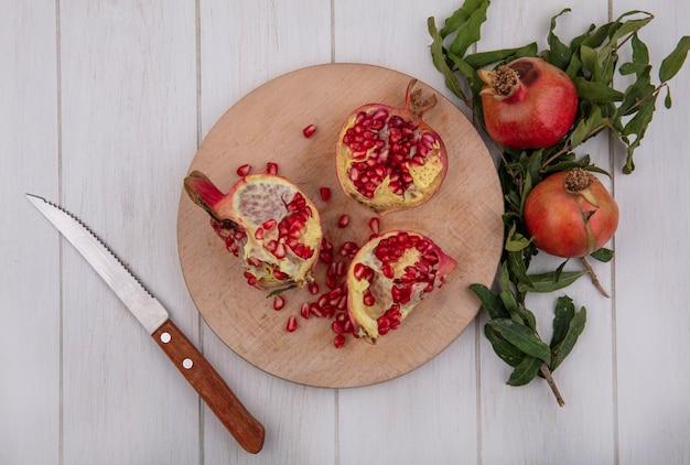 Bovenaanzicht granaatappels op snijplank met mes en takken van bladeren op witte achtergrond