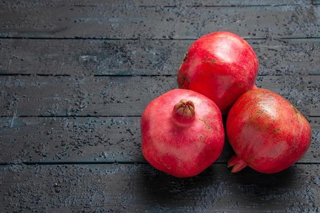 Bovenaanzicht granaatappels op tafel drie rijpe rode granaatappels rechts van grijze tafel