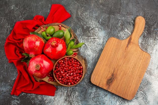 Bovenaanzicht granaatappels snijplank granaatappelpitjes en granaatappel op het tafelkleed