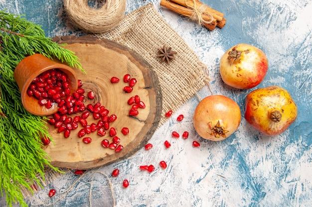 Bovenaanzicht granaatappels verspreid granaatappel zaden in kom op boom houten bord stro draad kaneel anijs zaden boomtak op blauw-witte achtergrond