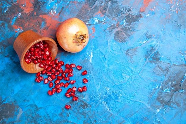 Bovenaanzicht granaatappelzaden in kleine houten kom een granaatappel op blauwe achtergrond met kopieerruimte