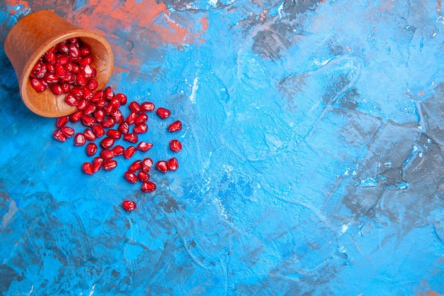 Bovenaanzicht granaatappelzaden in kleine houten kom op blauwe achtergrond met vrije plaats