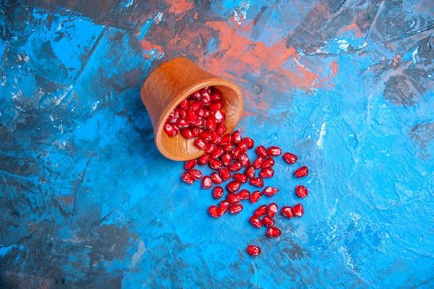 Bovenaanzicht granaatappelzaden in kleine houten kom op blauwe achtergrond vrije plaats