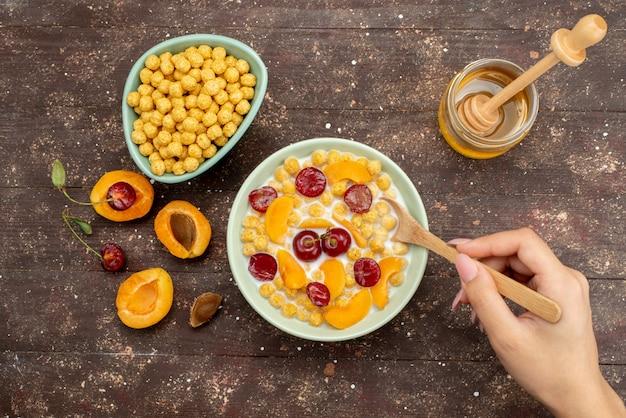 Bovenaanzicht granen met melk in plaat met vers fruit mengen door vrouw op hout, cornflakes ontbijtgranen