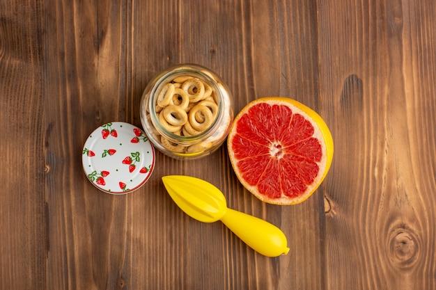 Bovenaanzicht grapefruit en crackers op het bruine bureau
