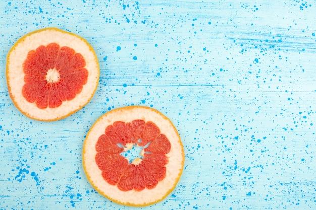 Bovenaanzicht grapefruit gesneden ringen zacht rijp op de heldere blauwe achtergrond