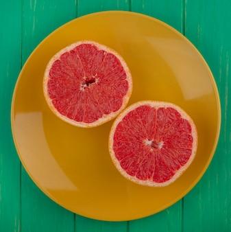Bovenaanzicht grapefruit helften op gele plaat op groene achtergrond