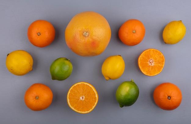 Bovenaanzicht grapefruit met sinaasappels, citroenen en limoenen (lemmetjes) op grijze achtergrond
