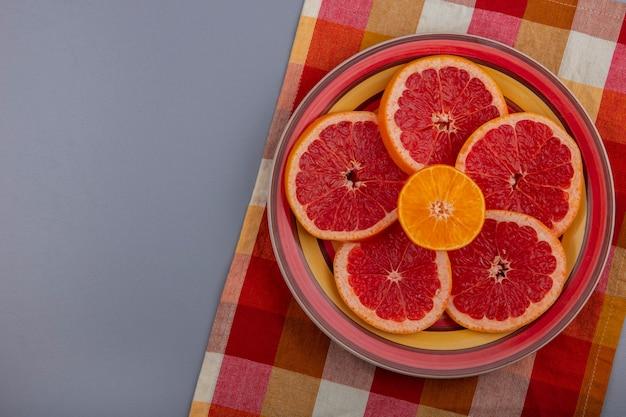 Bovenaanzicht grapefruit plakjes op een plaat op een geruite veelkleurige handdoek op een grijze achtergrond
