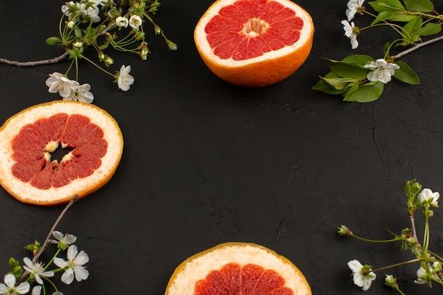 Bovenaanzicht grapefruits gesneden sappige mellow op het donkere bureau