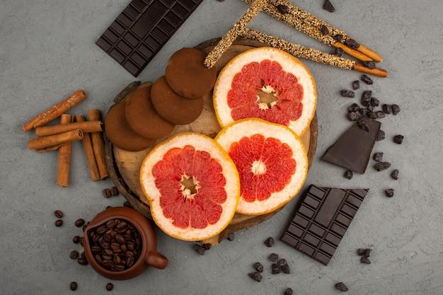 Bovenaanzicht grapefruits koekjes chocolade gesneden sappig op het grijze bureau