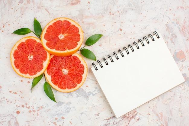 Bovenaanzicht grapefruits plakjes met bladeren een notitieblok op naakt oppervlak