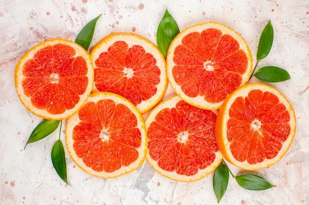 Bovenaanzicht grapefruits plakjes met bladeren op naakt oppervlak