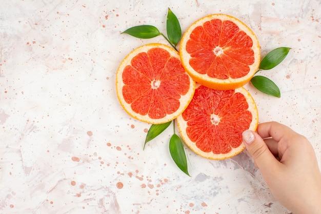 Bovenaanzicht grapefruits plakjes vrouw hand nemen grapefruit plak op naakt oppervlak vrije ruimte