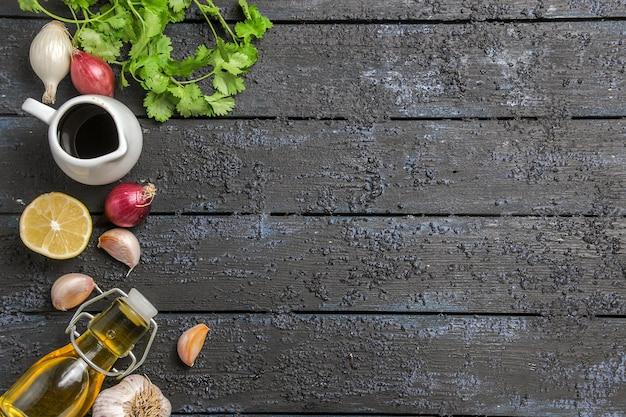 Bovenaanzicht greens en citroen met knoflook en olie op donker bureau