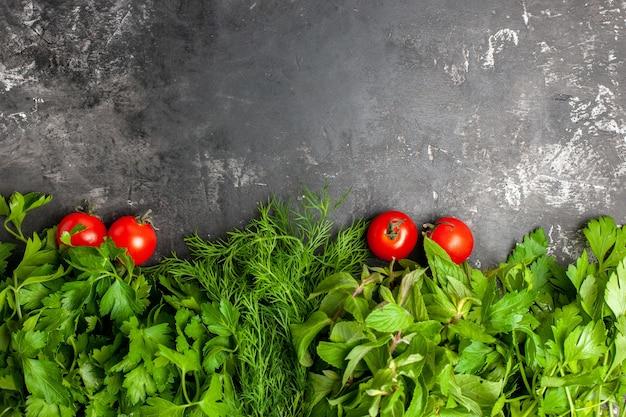Bovenaanzicht greens en tomaten op donkere achtergrond met kopieerruimte