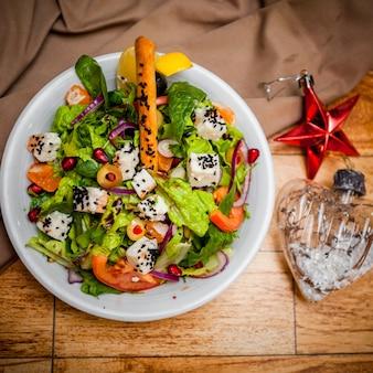 Bovenaanzicht griekse salade met kerst speelgoed in ronde witte plaat op tafel