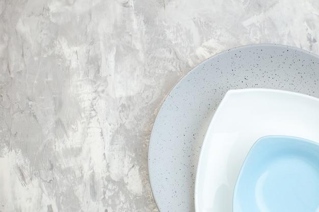 Bovenaanzicht grijze plaat met blauwe en witte plaat op lichte ondergrond keuken dames eten horizontale glazen maaltijdkleuren