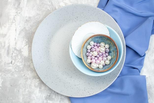 Bovenaanzicht grijze plaat met kleine blauwe plaat en kralen op lichte ondergrond keuken dames eten horizontale vrouwelijkheid glas maaltijd kleur