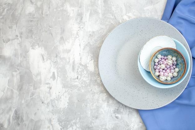 Bovenaanzicht grijze plaat met kleine blauwe plaat en kralen op lichte ondergrond keuken dames eten vrouwelijkheid glas maaltijd kleur