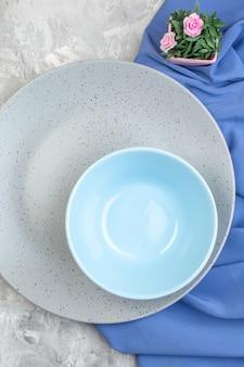 Bovenaanzicht grijze plaat met kleine blauwe plaat op lichte ondergrond keuken dames horizontaal eten vrouwelijkheid kleur glas maaltijd
