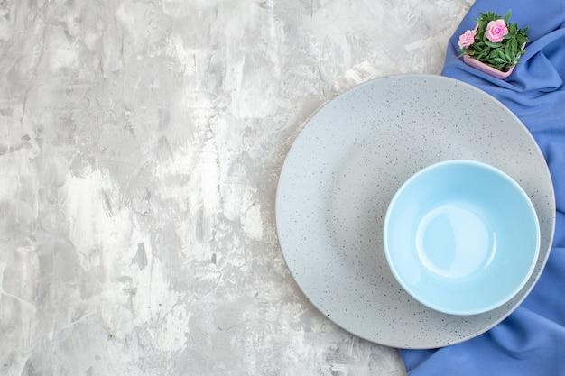 Bovenaanzicht grijze plaat met kleine blauwe plaat op lichte ondergrond keuken dames horizontaal voedsel familie vrouwelijkheid kleur glas maaltijd