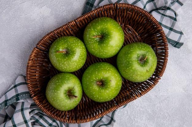 Bovenaanzicht groene appels in een mand op een groen geruite handdoek