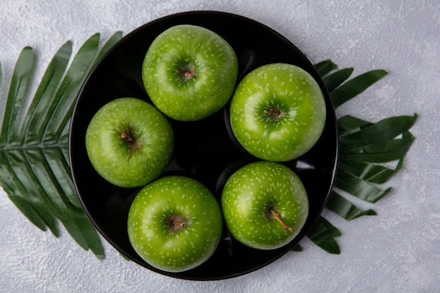 Bovenaanzicht groene appels op een zwarte plaat op takken met bladeren op een witte achtergrond