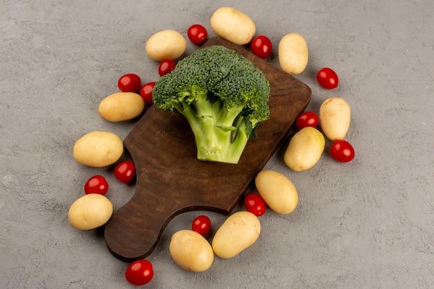 Bovenaanzicht groene broccoli samen met aardappelen en rode kerstomaatjes op de grijze vloer