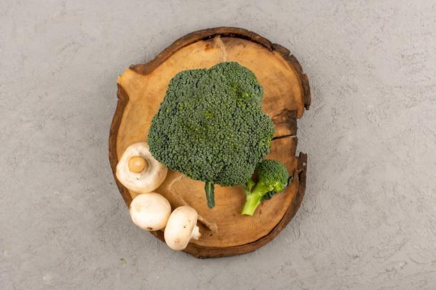 Bovenaanzicht groene broccoli samen met champignons op de grijze vloer