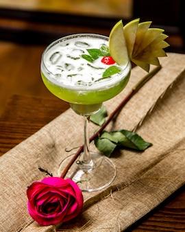 Bovenaanzicht groene cocktail met ijs en decor met plakjes appel munt kers en roze roos op tafel