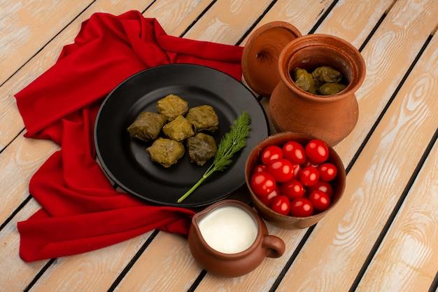 Bovenaanzicht groene dolma in zwarte plaat samen met rode kerstomaten en yoghurt op het bruine houten bureau