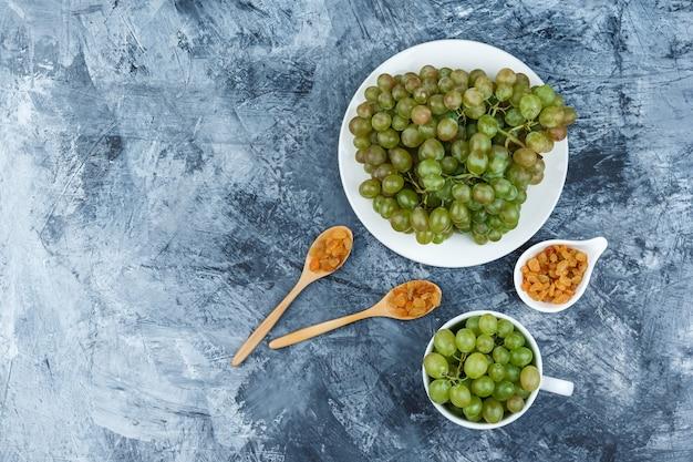 Bovenaanzicht groene druiven in witte plaat en beker met rozijnen op grungy gips achtergrond. horizontaal