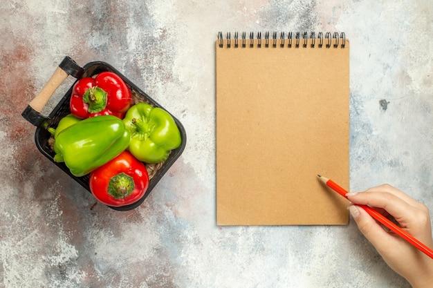 Bovenaanzicht groene en rode paprika in kom een notebook rode pen in vrouwelijke hand op naakt oppervlak