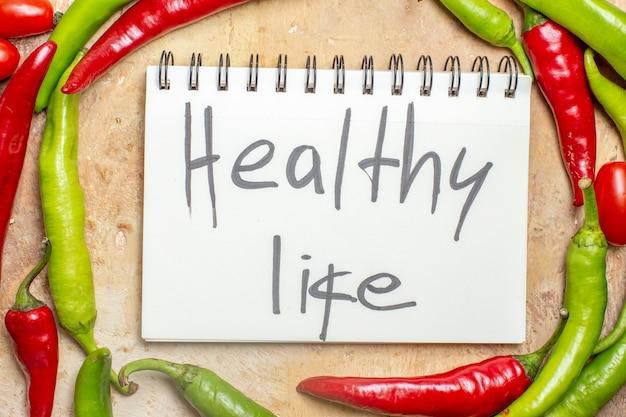 Bovenaanzicht groene en rode paprika's gezond leven geschreven op kladblok op amberkleurige achtergrond